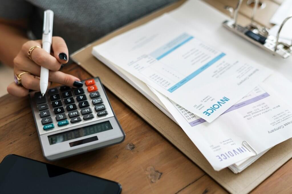 a woman with a calculator paying bills