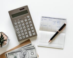paying bills with calculator and checkbook