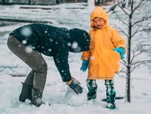 father making snowman with son