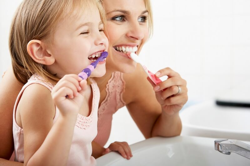 Mother And Daughter Brushing Teeth Together to save money at the dentist