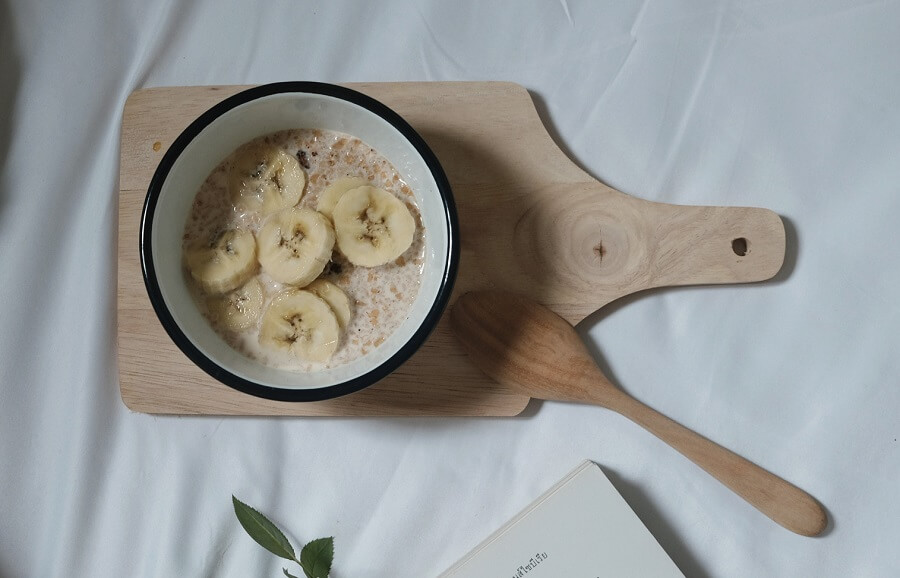 A bowl of warm homemade oatmeal with fruit topping is a healthy Breakfast.