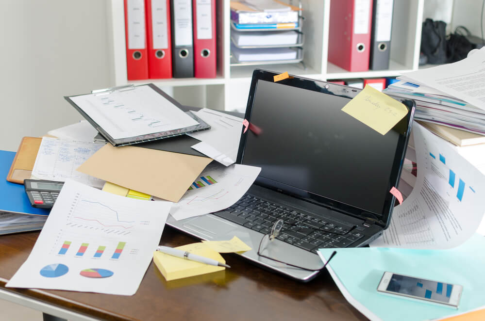 A messy work desk that needs to be organized