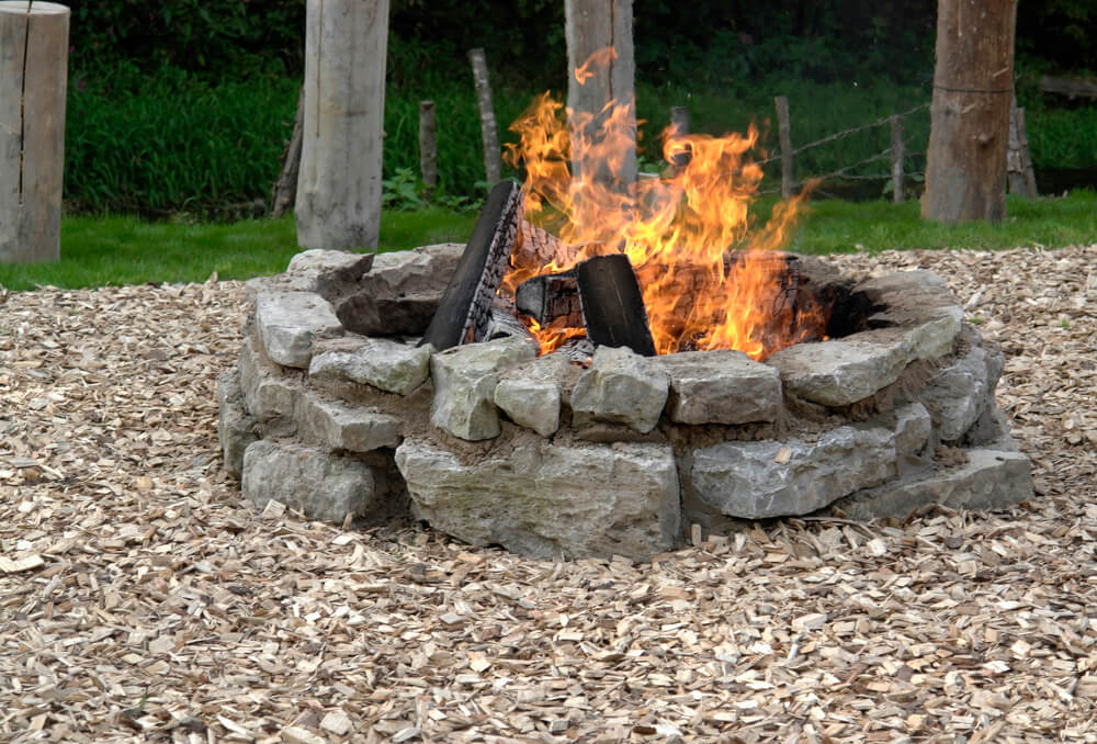 a budget firepit made from rocks in a backyard