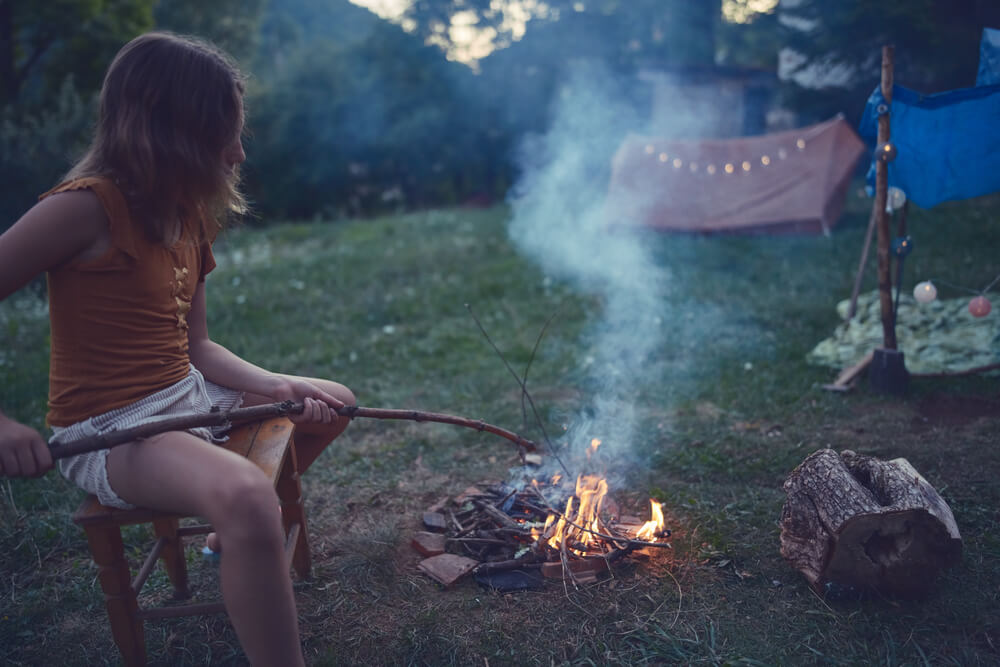 a girl at a campfire with tent in background