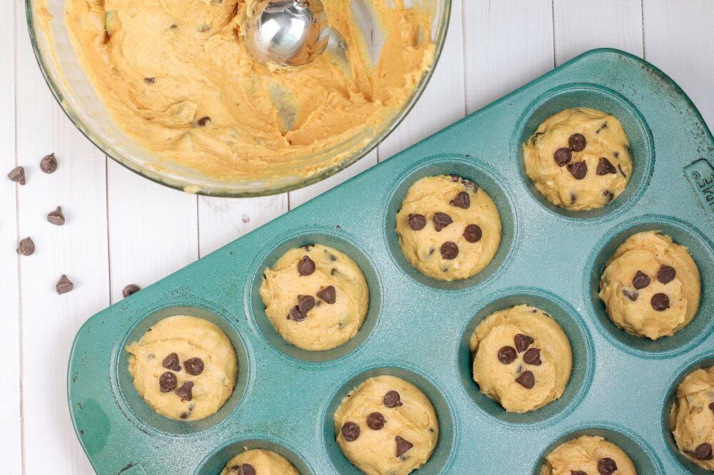 Pumpkin muffin mix being put into muffin tins.