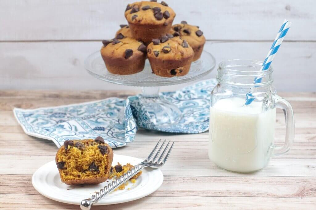Healthy Pumpkin Chocolate Chip muffins sit on a cake stand with a glass of milk on the table.