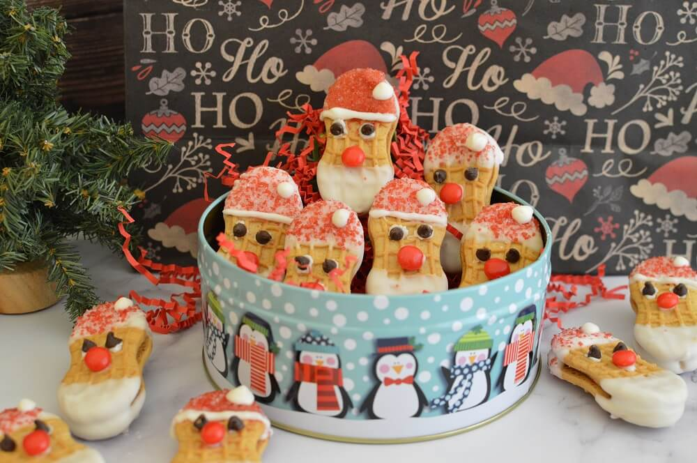 Santa Nutter Butter cookies arranged in a blue tin with cartoon penguins.